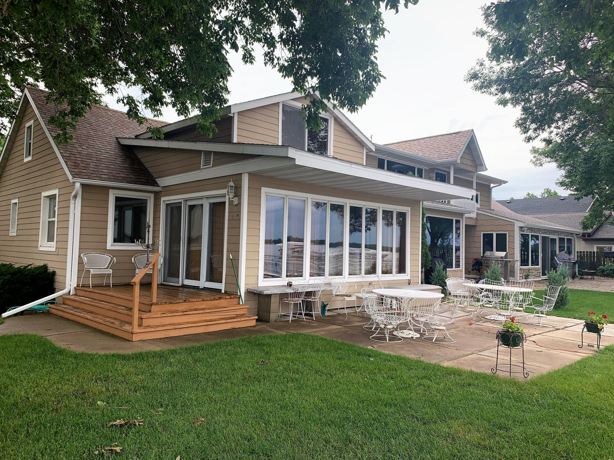 "Lakefront home with wonderful southern exposure, no steps to the lake and close to downtown. Casual comfort with 2 bedrooms and bath on main level and Master bedroom with bath upstairs. Spacious living room area with room for table and chairs for playing cards,puzzles, etc. on rainy days and still have view of lake. Formal dining room with plenty of space for entertaining meal time guests.Wonderful large patio, and green space on lakeside. The newer dock is included. Room for grill on the deck. Attached oversized single garage with pull down stairway with attic area above that could possibly be additional upstairs bonus room accessed from the 2nd floor if renovated. Enjoy this affordable lakefront home as a permanent residence or 2nd home get-a-way. Being sold in ""as is, where is""condition with no warranties or guarantees expressed or implied."